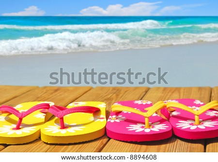 Colorful flip flop sandals on boardwalk with ocean in distance - stock photo