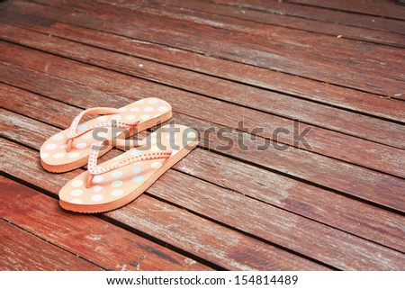 Colorful flip flop sandals on wood background. - stock photo