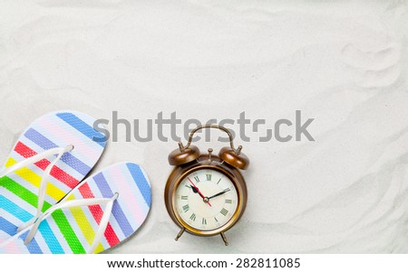 Colorful flip flops and classic alarm clock on white sand. Photo with high angle view.