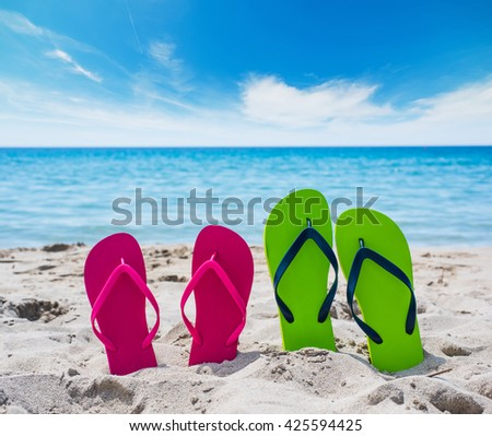 colorful flip flops on the sand - stock photo