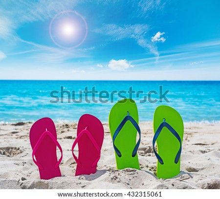 colorful flip flops on the sand in Sardinia, Italy - stock photo