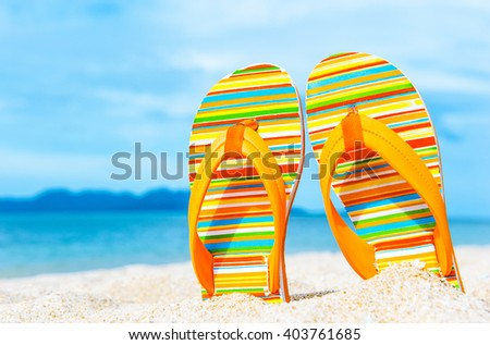Colorful flip flops on the sandy beach. Vacation concept