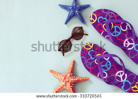 colorful flip flops, starfish and sunglasses on  wooden background