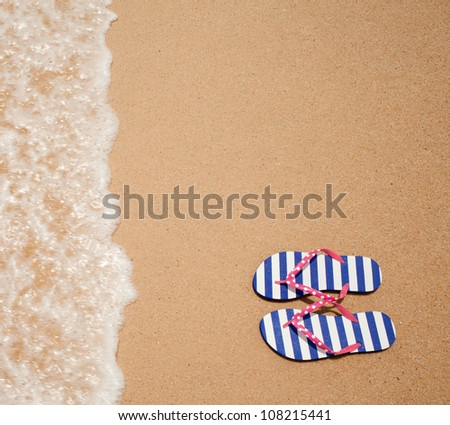 Colorful flipflop pair on sea beach top view - stock photo