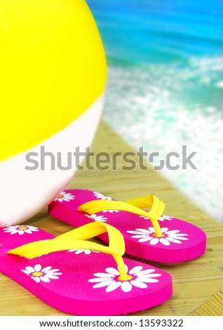 Colorful flipflop sandals and inflatable beach ball by ocean - stock photo