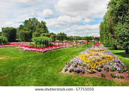 Colorful flower beds arranged by figures on the lawn - stock photo