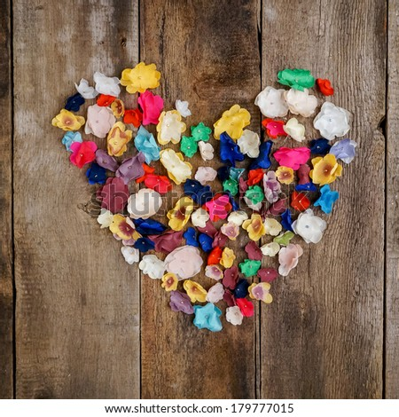 Colorful flower heart on old wooden background - stock photo