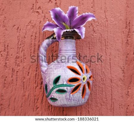Colorful Flower vase on a red wall in a mexican house   - stock photo