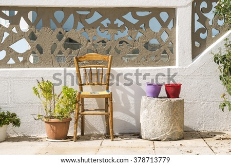 Colorful flowerpots and chair on street of typical greek traditional village with white houses on Karpathos Island, Greece. - stock photo