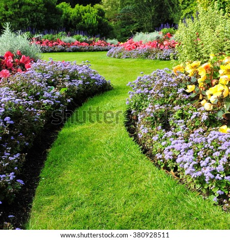 Colorful Flowers and a Winding Grass Lawn Path in a Beautiful Garden - stock photo