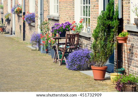 Colorful flowers before historic facades of the Begijnhof in the Dutch city of Breda. - stock photo