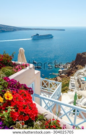 Colorful flowers, buildings and cruise ship on the sea in Oia town, Santorini island, Greece - stock photo
