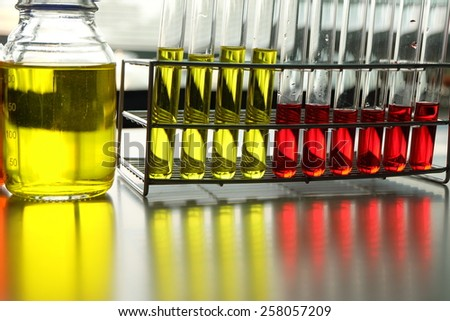 Colorful fluid in bottle and test tube for laboratory use on table laboratory - stock photo