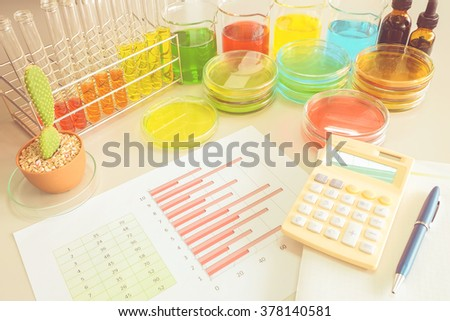 Colorful fluid in glass ware and graph for laboratory  with vintage color style - stock photo
