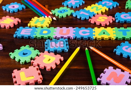Colorful foam puzzle letters with pencils on wooden background, education concept - stock photo