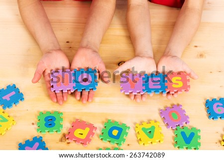 Colorful foam puzzle letters words yes and no in kid's hands on wooden background - stock photo