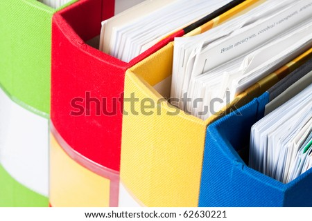 Colorful folders full of papers upper view