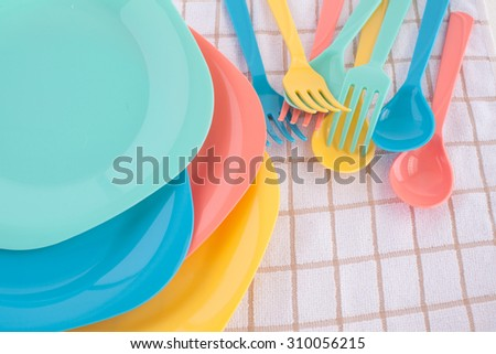 colorful fork ,knife and spoon put on colorful plastic plate at tablecloth