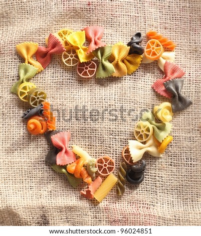 Colorful frame on hessian material of variously shaped pastas including bowtie, wheels, and spirals. - stock photo