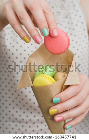 Colorful french dessert macaroons in the hands of girl - stock photo
