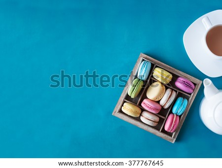 Colorful French macaroons in a wooden gift box. Cup of tea and teapot. Top view. - stock photo