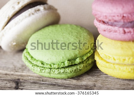 Colorful French macaroons on a dark  wooden background, selective focus - stock photo