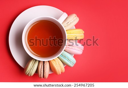Colorful French Macaroons with Cup of Tea on red background - stock photo