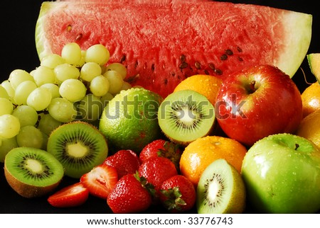 Colorful fresh group of fruits over a black background. Look at my gallery for more fresh fruits and vegetables. - stock photo