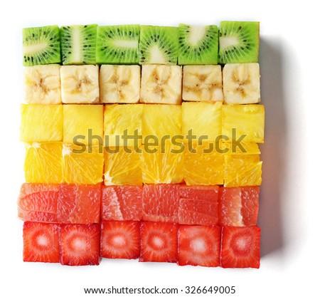 Colorful fresh sliced fruit cubes isolated on white - stock photo
