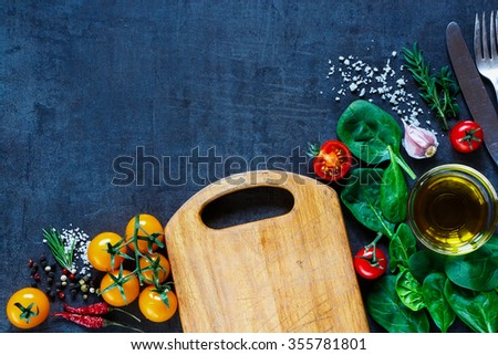 Colorful fresh vegetables and herbs ingredients for tasty cooking around rustic wooden cutting board over dark vintage table, top view. Healthy food or vegetarian eating concept. Copy space. - stock photo