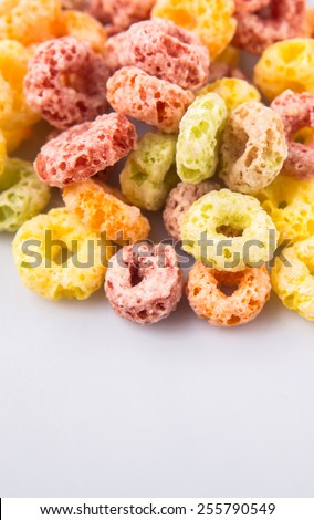 Colorful fruit flavored loops shaped cereal over white background - stock photo