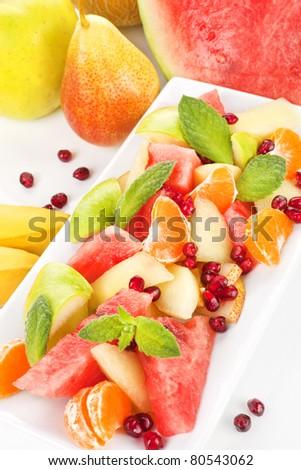 Colorful fruit salad. Apple, pear, banana, tangerine, pear and pomegranate fruit salad. Fresh summer eating. - stock photo
