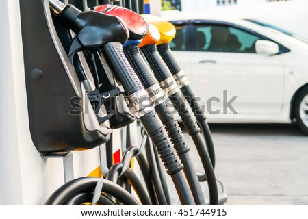 Colorful fuel nozzles on the dispenser machine in the petrol station - stock photo
