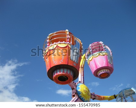 Colorful funfair ride against blue sky - stock photo