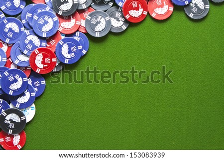 Colorful gambling chips on green felt background with copy space - stock photo