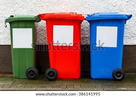 Colorful garbage trash cans aligned near the wall - stock photo