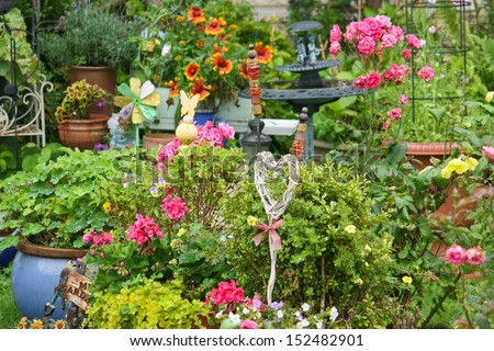 colorful garden in summer with blooming flowers, decorations and plants