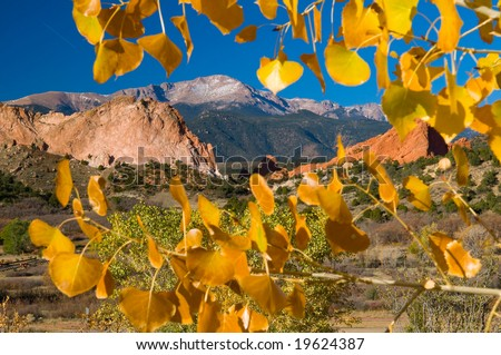 Colorful Garden of the Gods Park near Colorado Springs, Colorado with golden leaved aspen trees and snow covered Pike's Peak - stock photo