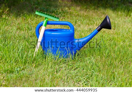 Colorful garden tools, a blue plastic watering can.