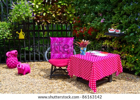 Colorful garden with pink chair and table - stock photo