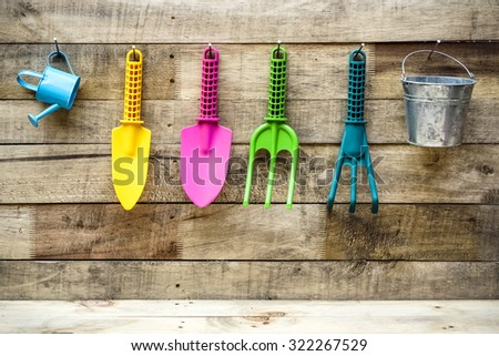 colorful gardening tools on wood background - fork, shovel, rake, bucket, watering can - stock photo