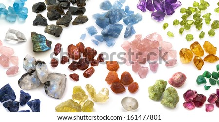Colorful gemstones background. Large variety of natural raw, uncut precious and semiprecious gems on the white background. - stock photo