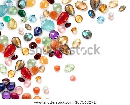 Colorful gemstones composition with empty white space. Many real gems: garnet, sapphire, aquamarine, chrysoprase, moonstone rainbow, citrine, amethyst, prehnite, chalcedony, rose quartz, amazonite ... - stock photo