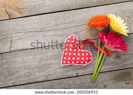 Colorful gerbera flowers and Valentine's day heart toy. On wooden background with copy space - stock photo
