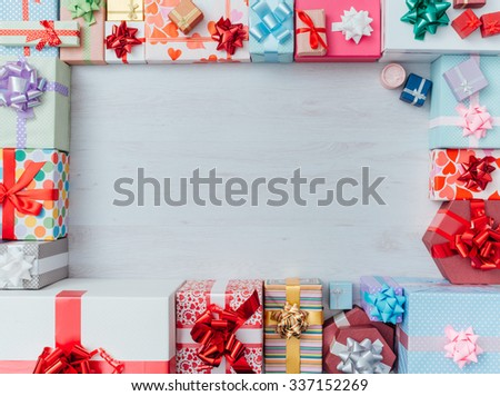 Colorful gift boxes framing a blank copy space on a desktop, top view, Christmas and celebrations concept - stock photo