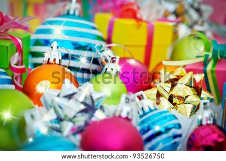 Colorful gift boxes intermingled with shining Christmas balls and bows.