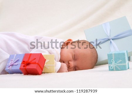 Colorful gift boxes with sleeping baby - stock photo