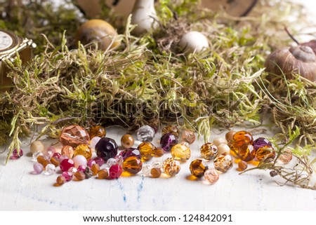 colorful glass beads with mushrooms and moss on white wooden table - stock photo