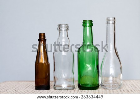Colorful glass bottles (brown, green, transparent). empty glass. Gray background. - stock photo