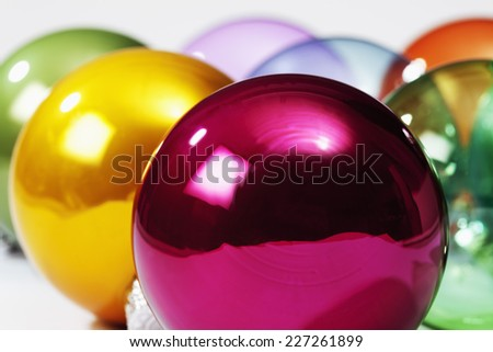 Colorful glass christmas baubles on wooden background